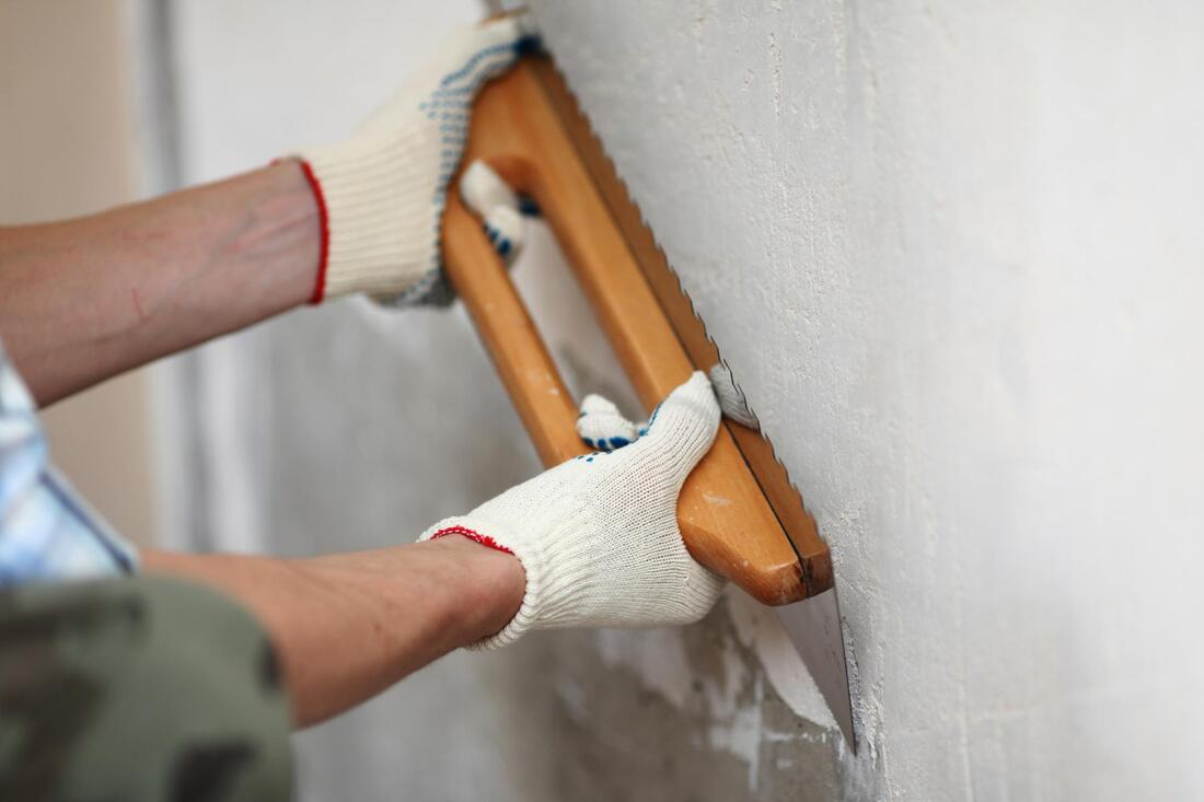 man wearing a gloves and using a plastering tool on a wall